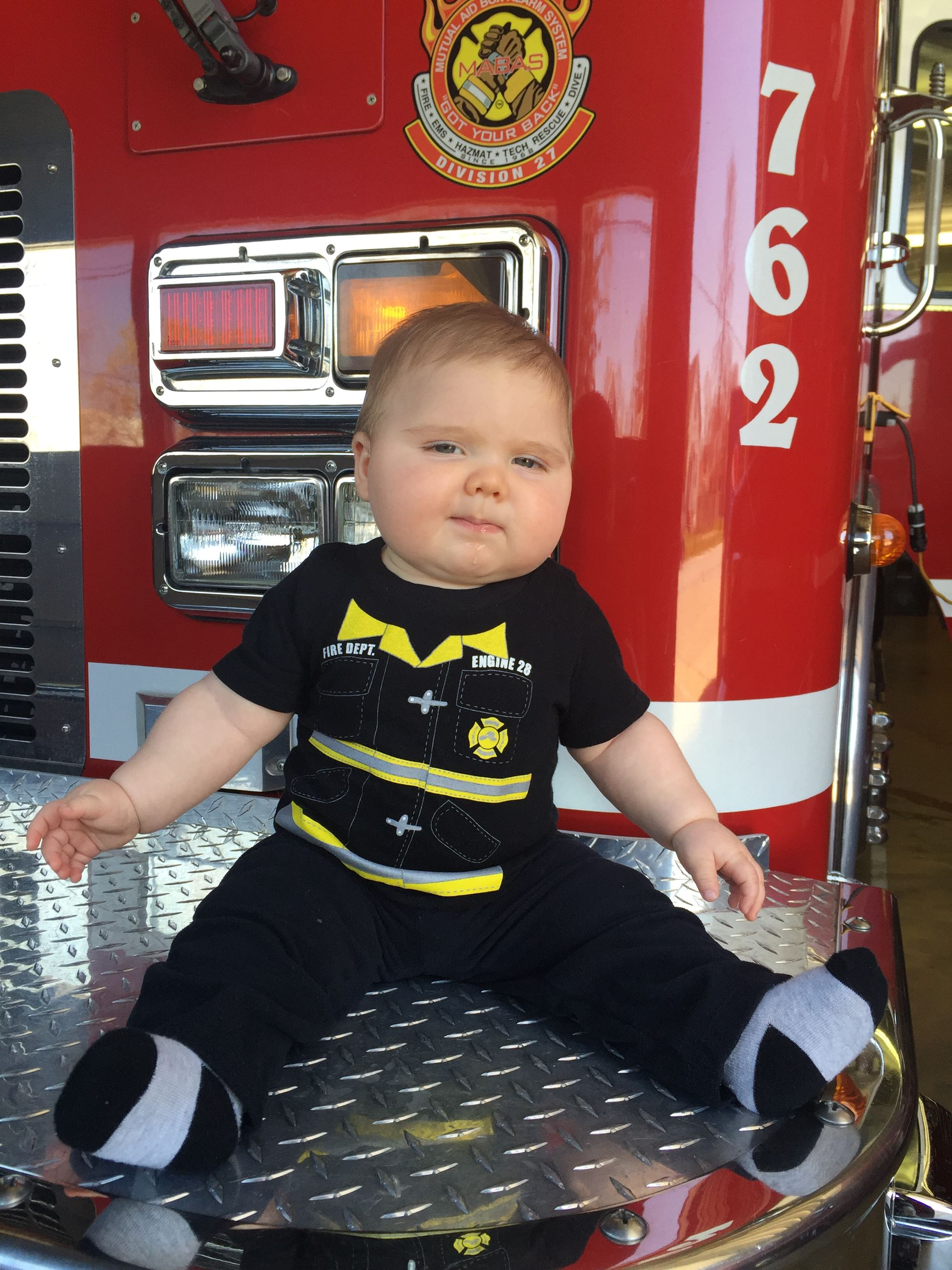 Baby dressed in a onesie that looks like a firefighter's uniform